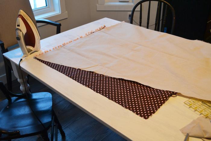 ein boden aus holz, ein weißer tisch und drei schwarze stühle, zwei kleine fenster und weiße wände, ein stoff mit vielen kleinen pinken punten