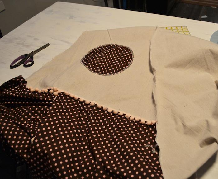 spielzelt tipi, ein weißer tisch miu einer großen schwarzen schere und mit einem kinderzelt tipi aus einem stoff mit vielen kleinen pinken punkten
