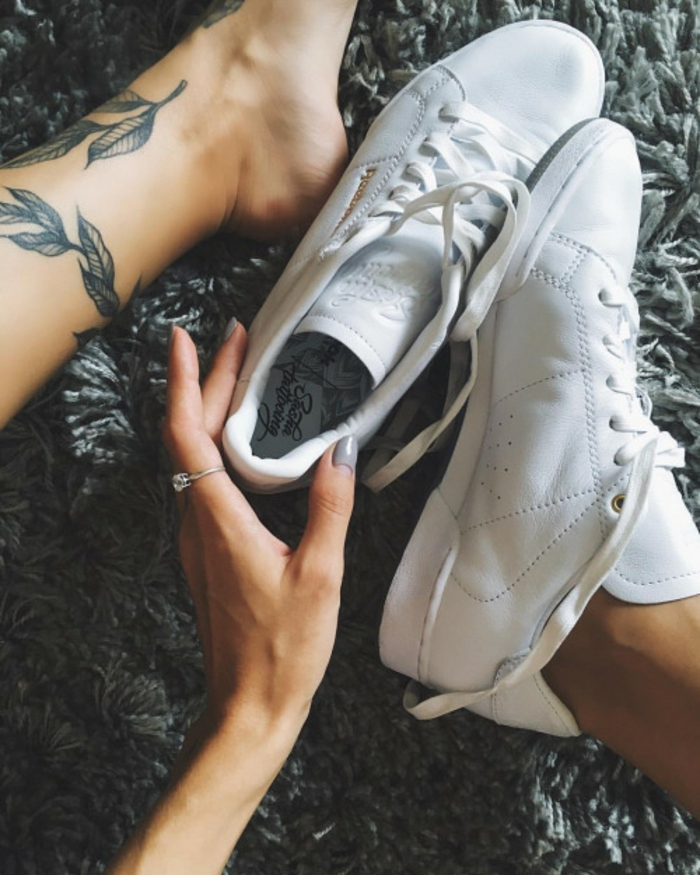 blumen tattoo am fuß, sneakers, turnschuhe in weißer farbe, frau mit großem ring am zeigefinger