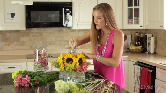 blumengestecke ideen, sonnenblumen, eine frau mit pinkem top, rosa bluse, blumenstrauß machen