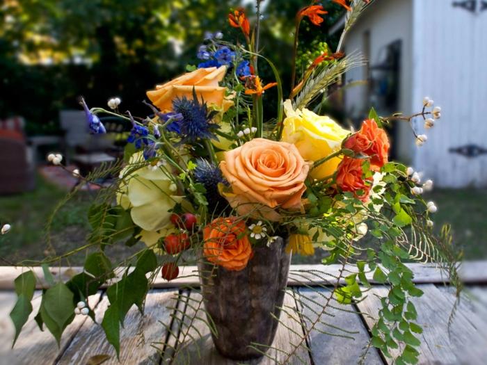 tischdeko selber machen, herbstdeko idee, rosen, grüne stängel von blumen, blaue blümchen. bunter strauß