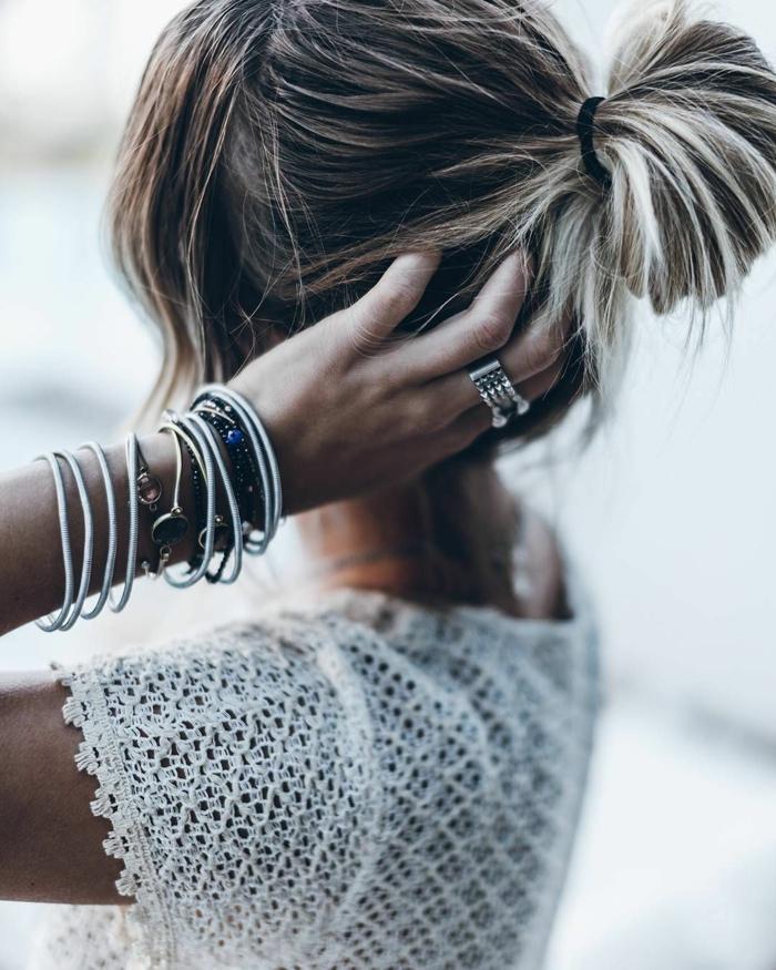 weiße Bluse, ein großer Ring, Dutt Haare mit grauen Highlights