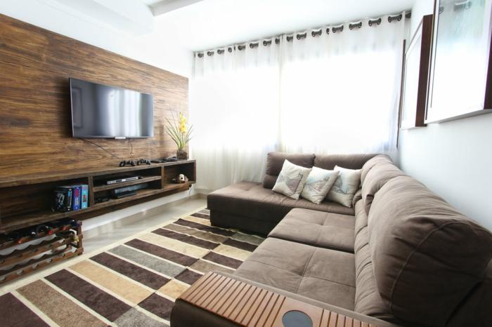 ein braunes Sofa, brauner Teppich, Fernsehwand ais Holz, Wohnzimmergestaltung