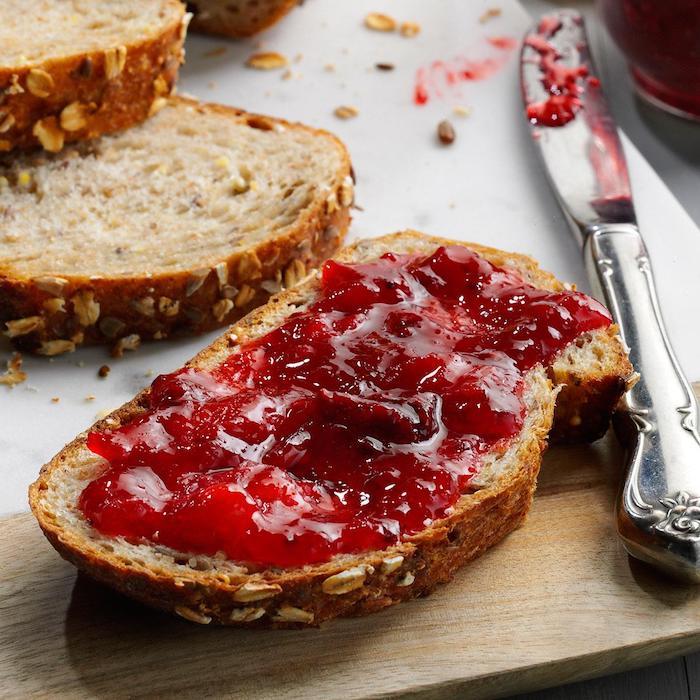 ein holzbrett und ein messer, ein tisch und brot mit einer roten erdbeer rhabarber marmelade, rezepte mit rhabarber