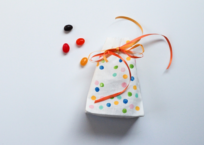 weiße Tüte mit orangen Schleife gebunden, voller Bonbons mit bunten Flecken, kleine Geschenktüten