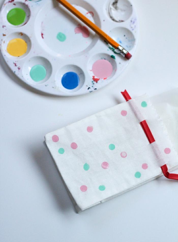eine weiße Tüte mit bunten Flecken, Texilfarbe in einer Palette, Gummi als Pinsel
