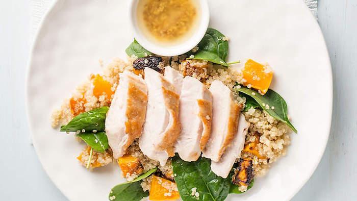 diät abendessen, runder teller, fleisch mit quinoa und grünen salatblättern, soße