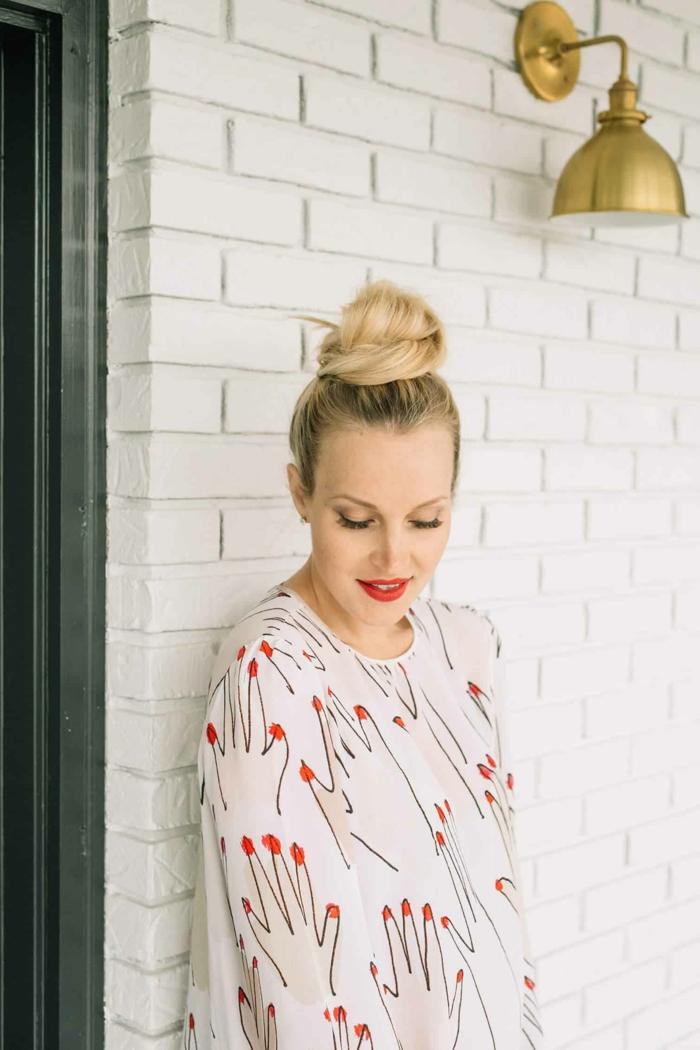 ein blonder messy Dutt, eine hübsche Frau, weiße Bluse mit interessanten Motiven