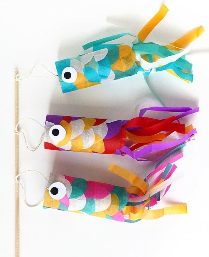 drei bunte Fische auf einem Stock zum Spielen, Basteln mit Klopapierrollen