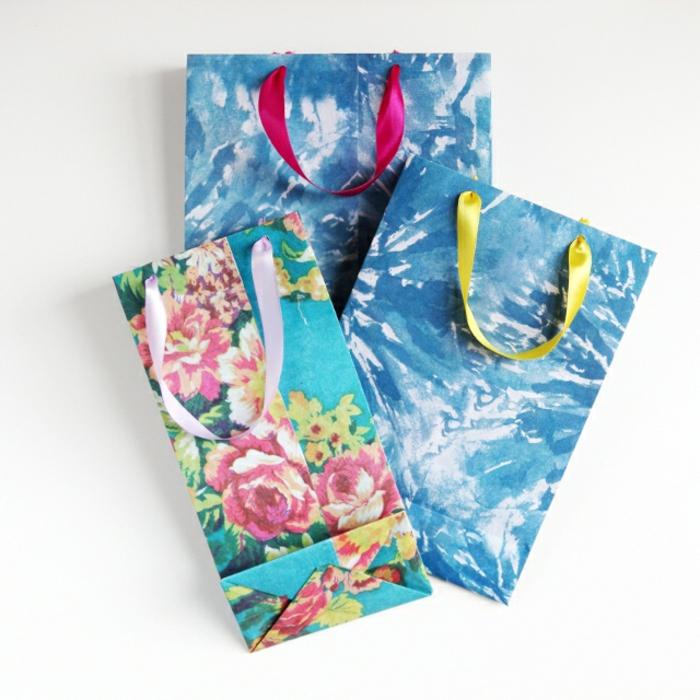 drei blaue Tüten, zwei mit abstrakten Motiven, eins mit Blumenmotiven, Geschenktüten basteln