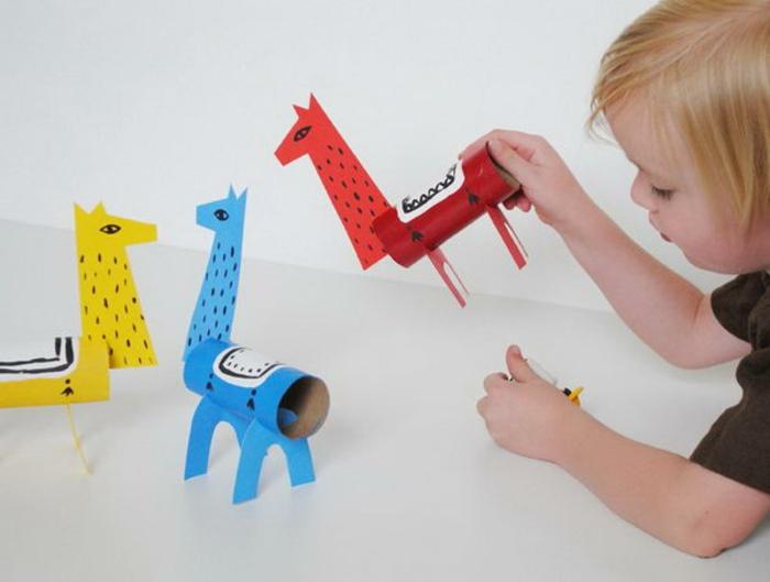 das Kind spielt mit drei Giraffen, Blau, Rot und Gelb, was kann man aus Klopapierrollen machen
