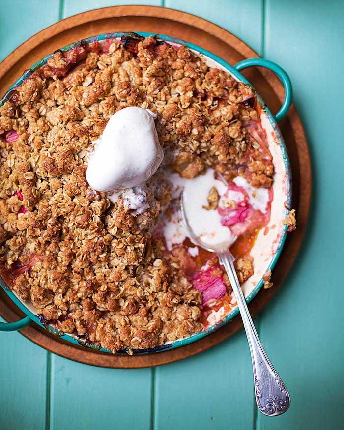 eine grüne pfanne mit einem rhabarber kuchen mit eis und ein löffel, ein tisch aus holz, rhabarber crumble rezepte