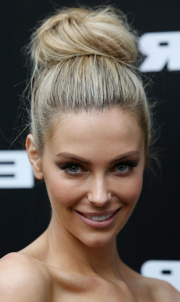 eine niedliche Prominente mit blondem Haar und blauen Augen, Dutt Haare