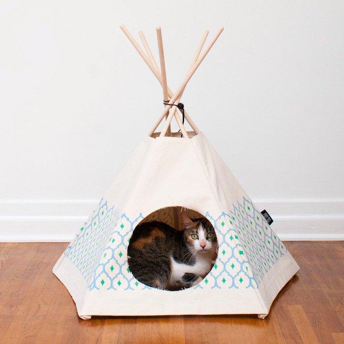 ein kleines weißes zelt für katmzen und mit vielen kleinen stöcken aus holz, eine katze mit grünen augen, eine weiße wand und ein boden aus holz, ein tipi bauen