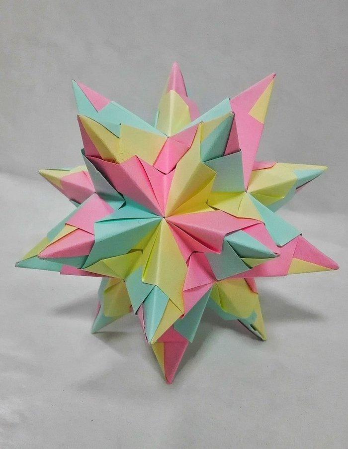 ein großer bunter bascetta stern mit grünen, violetten und gelben strahlen aus papier, origami sterne falten