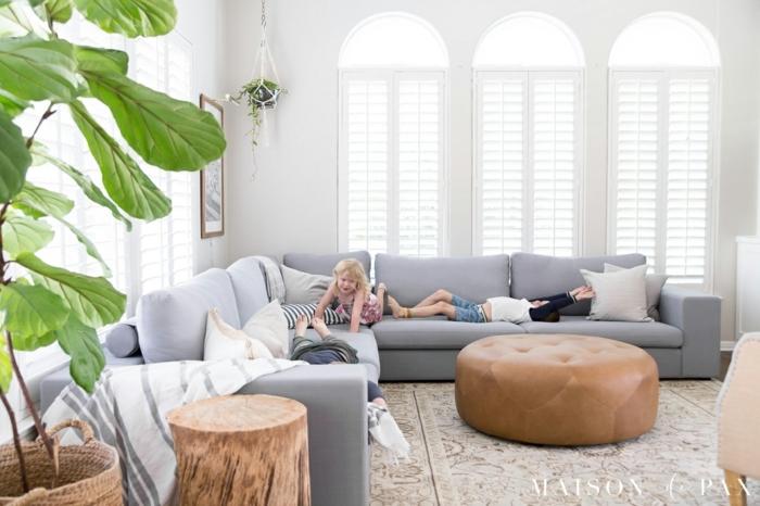 eine blaue Couch, ein Perserteppich, Wohnzimmer einrichten, Rollos an Fenstern