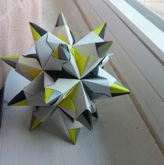 ein fenster und ein großer grauer origami stern, bascetta stern basteln, ein bascetta stern mit grauen und grünen strahlen aus papier