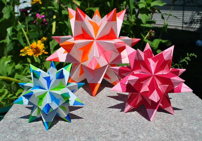 drei große blaue, violette und orange bascetta sterne aus papier und mit blauen, grünen, pinken, orangen und roten strahlen, bascetta stern papier, ein garten mit gelben und violetten blumen mit grünen blättern