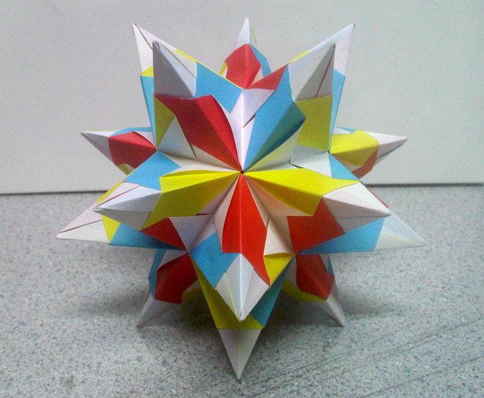 ein großer weißer bascetta stern aus papier und mit blauen, roten, gelben und weißen strahlen aus papier, origami falten, anleitung bascetta stern