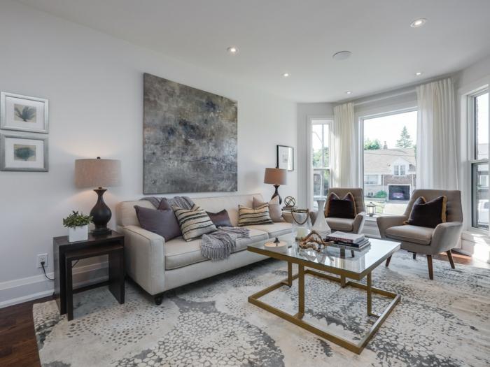 ein großes graues Bild, Sofas und zwei Sessel, schwarz weißer Teppich, Wandfarbe Hellgrau