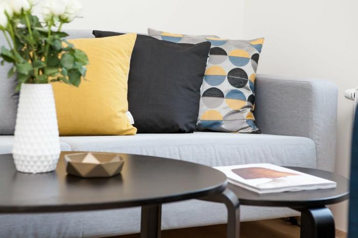 moderne Wohnzimmer, zwei Couchtische, Sofa mit drei Kissen, graue Wandfarbe