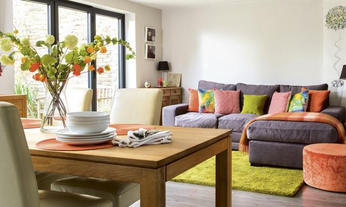 eine Wohnküche mit einem grauen Ecksofa, dekoriert mit bunten Kissen, moderne Wohnzimmer