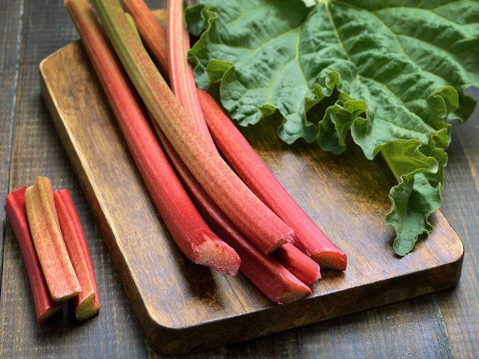 ein tisch aus holz und ein braunes holzbrett mit langen roten geschnittenen rhabarber pflanzen mit grünen blättern, rhabarber erntzeit