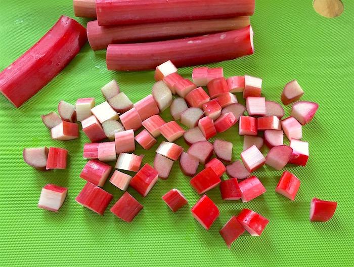 rhabarber erntzeit, ein grüner tisch und viele lange rote und genschnittene rhabarber pflanzen, rhabarber ernten, rezepte mit rhabarber pflanzen