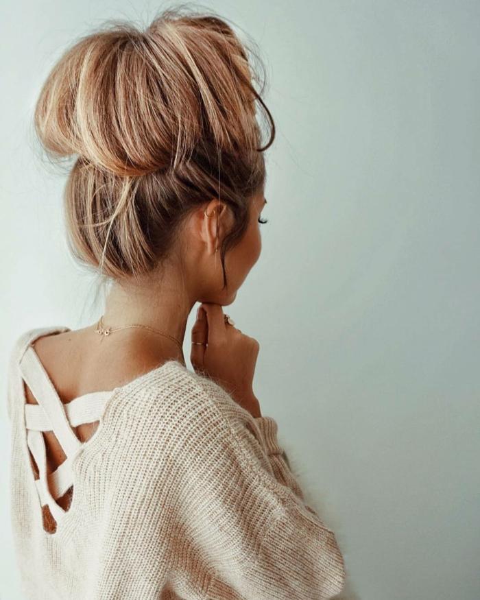 ein beiger Pullover, eine goldene Kette, rosa Haar, Dutt Haare