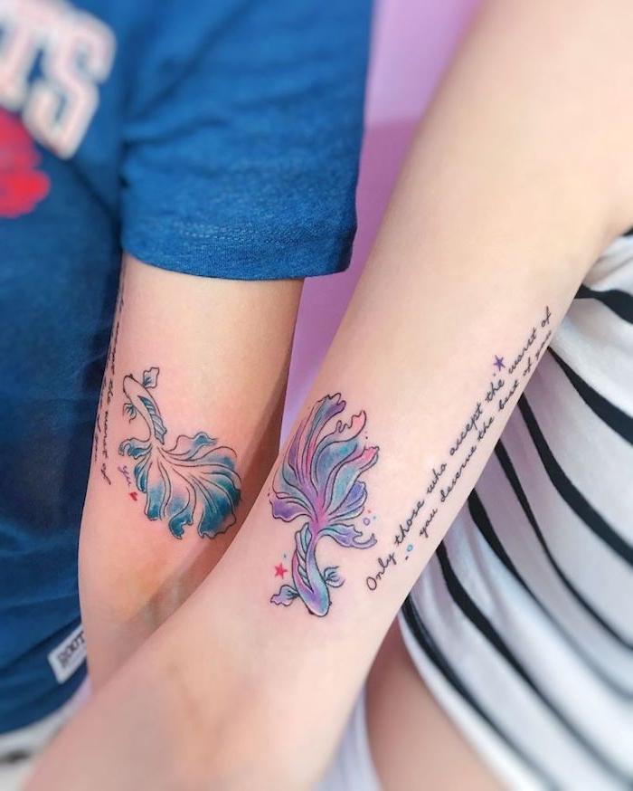 junge menschen mit händen mit zwei bunten watarcolor tattoos für paare mit zwei kleinen violetten und blauen fischen