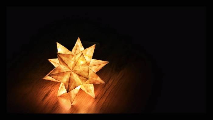 ein kleiner gelber origami papierstern mit leuchten und ein tisch aus holz, basteln mit papier, einen bascetta stern falten