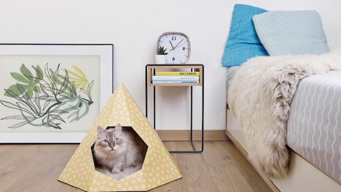 ein boden aus holz, ein bild mit großen grünen blättern, ein schlafzimmer mit einem bett mit grauen und blauen kissen, ein kleines gelbes zelt für katzen, eine katze und ein gelbes tipi