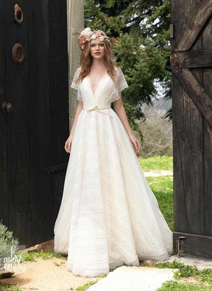 eine blonde Braut mit schönen Blumenkranz, langer Rock, weißer Gürtel, tiefer Ausschnitt