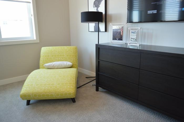 eine bequeme Leseecke, ein Regal, eine Stehlampe, Grautöne an den Wänden
