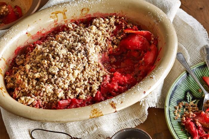 ein tisch aus holz und eine gelbe schüssel mit einem erdbeer rhabarber kuchen, rhabarber crumble, ein grüner teller mit roten erdbeeren