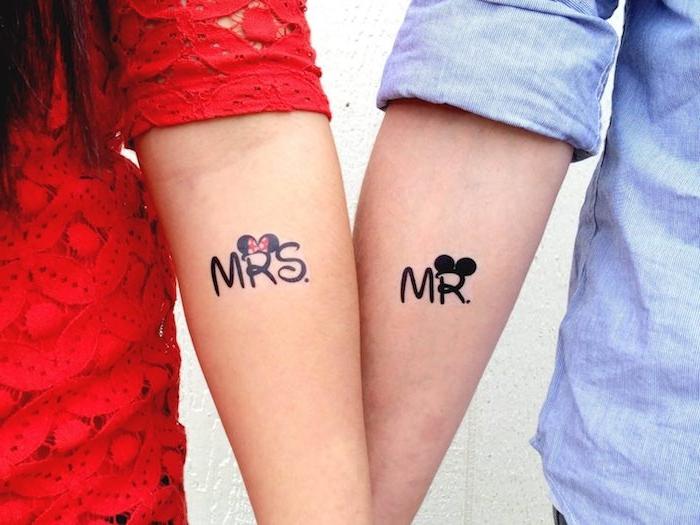 mrs and mr, zwei junge menschen mit händen mit kleinen schwarzen partnertattoos mit disney motiven und schwarzen mickey mouse ohren