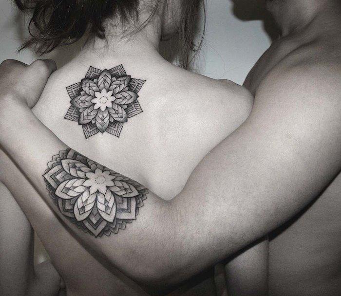 eine hand mit einem großen schwarzen mandala tattoo mit mandala blumen, tattoo partner, eine frau mit einer schwarzen tätowierungen auf dem rücken mit mandala blumen
