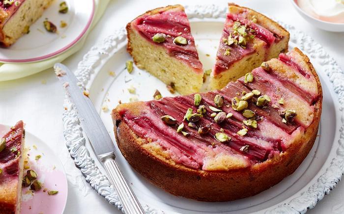 ein weißer teller mit einem messer aus metall und mit einem roten rhabarber kuchen, rezepte mit rhabarber