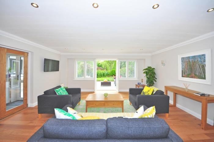 drei Sofa, Wohnzimmer Weiß Grau, Laminatboden, ein Tisch aus Holz