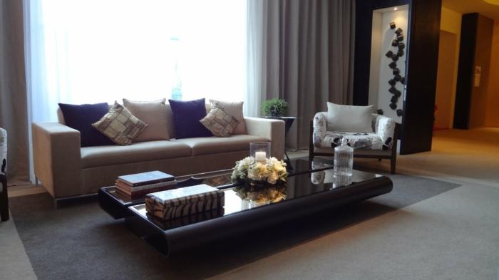 ein grauer Teppich, ein niedriger schwarzer Tisch, blaue Kissen, Wohnzimmer Design
