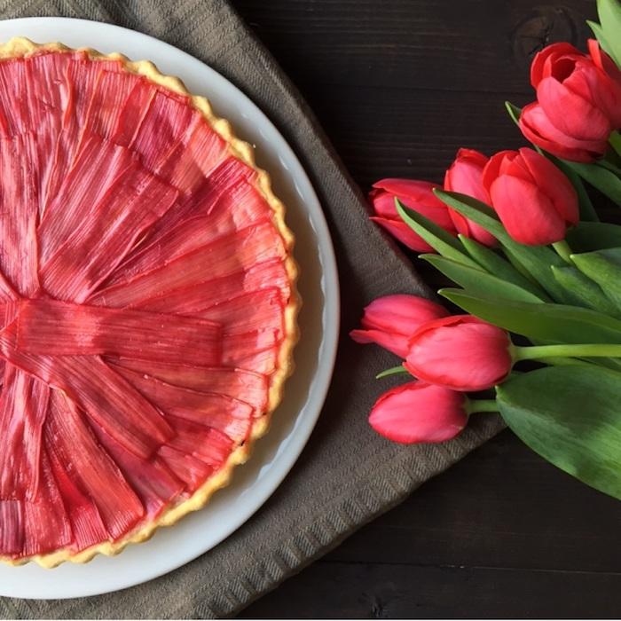 ein schwarzer tisch und eine decke, ein weißer teller mit einem großen roten rhabarber kuchen, viele rote tulpen mit grünen blättern, rhabarber rezepte