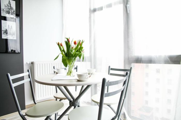 ein runder Tisch, eine Vase voller Tulpen, Grautöne an den Wänden