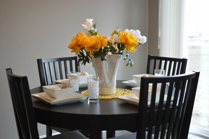 ein Esstisch in schwarzer Farbe, weiße und gelbe Blumen in einer Vase, Grautöne