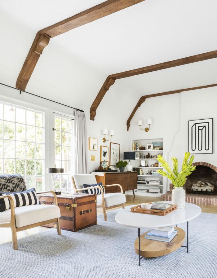 ein Kamin, zwei Sessel, ein runder Tisch in weißer Farbe, Wohnzimmer Design