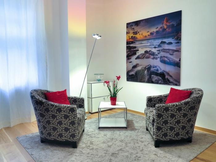 zwei graue Sessel mit roten Kissen, ein grauer Teppich, ein kleines Tischlein, Dekoideen Wohnzimmer