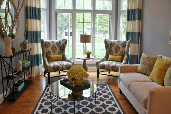 lange Vorhänge, zwei Sessel und ein Sofa, bunter Teppich, Wohnzimmer Design