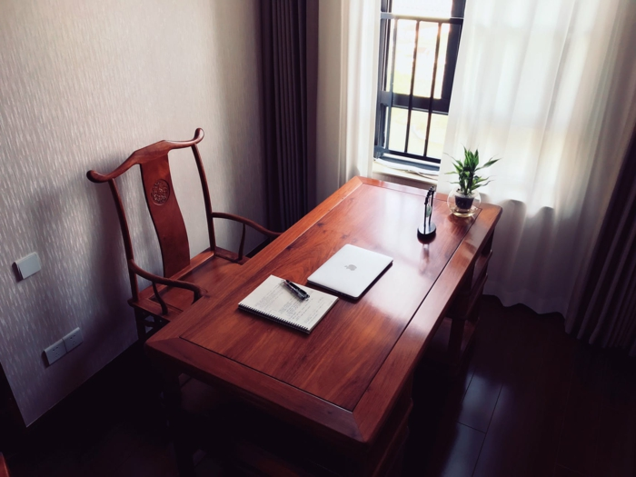ein Luxus Arbeitszimmer, eine weiße Gardine, schwarzer Laminatboden, Grautöne
