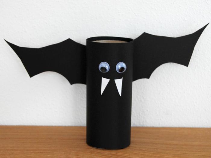 eine ganz schwarze Fledermaus, weiße Vampirezähne, große Augen, Bastelideen mit Klopapierrollen
