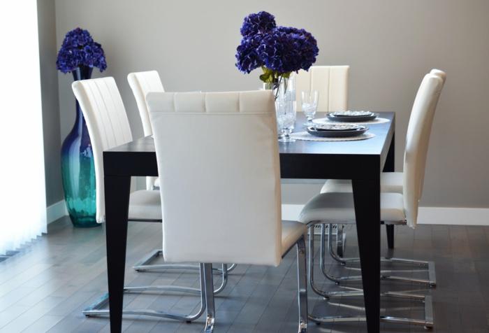 ein schwarzer Tisch, lila Blumen in Vasen, Laminatboden, Grautöne
