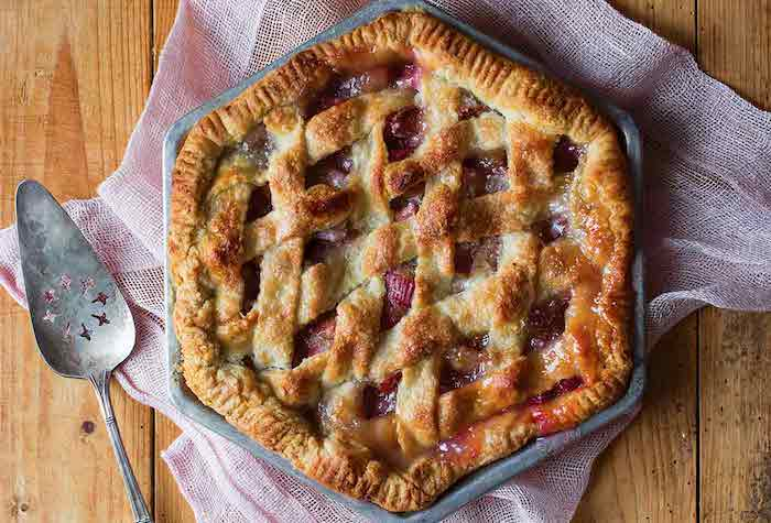 ein löffel aus metall und mit kleinen sternen, ein erdbeer rhabarber kuchen, ein tisch aus holz und mit einer pinken decke, rhabarber zubereiten